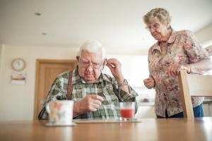 elderly man inserting his hearing aid