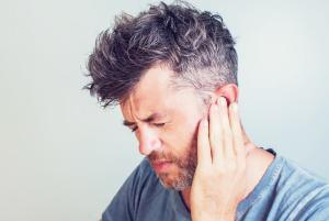 Man Holding Ear